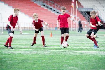 Full length portrait of row of teenage boys running in footbal field during match on outdoor stadium