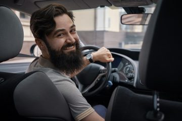 happy-charismatic-man-driving-a-car-7632MVJ